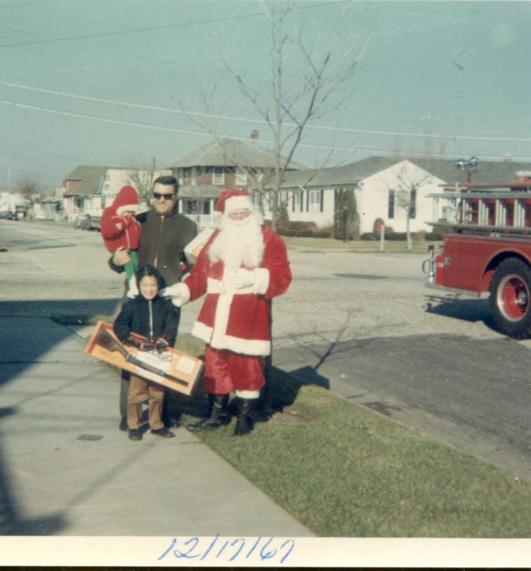 Taken outside the Vinci residence at 22nd & Central Aves. on December 17, 1967 of the North Wildwood Fire Department delivering toys to the pre-school children.  Pictured are Lew, Jr. and Joanne Vinci, and the late Lew Vinci, Sr. and Santa in the person of Tim O'Leary.
